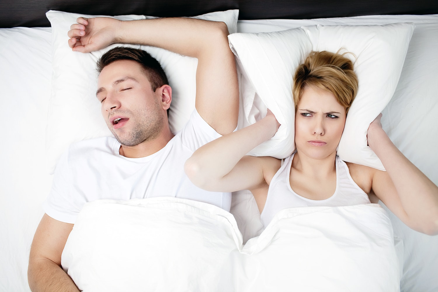 A couple in bed with the man snoring and the woman annoyed at the snoring man.